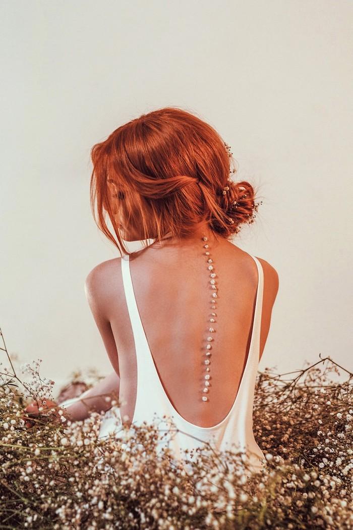 Haarfarbe Kupfer, lässige Hochsteckfrisur, weiße Blüten im Haar, weißes rückenfreies Kleid