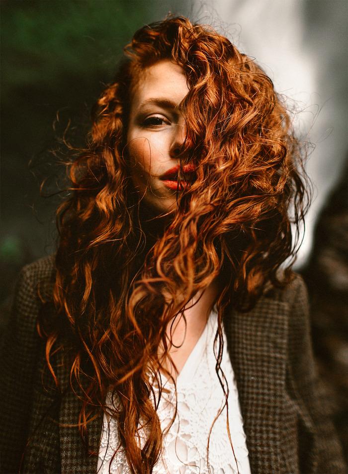Kupferfarbene wellige lange Haare, weißes Top mit Spitzenelementen und schwarzer Mantel