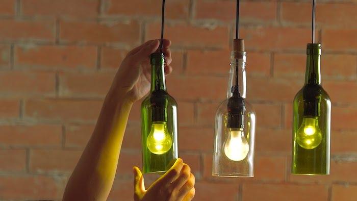 zwei hände und drei lampen aus alten grünen und weißen weinflaschen aus glas und mit drei glühbirnen, upcycling diy