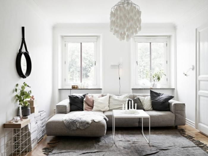deko wohnzimmer klein im skandinavischen stil, großes sofa als mittelpunkt des zimmers, dezente deko, blumen in topf, spiegel an der wand, kissen, fell