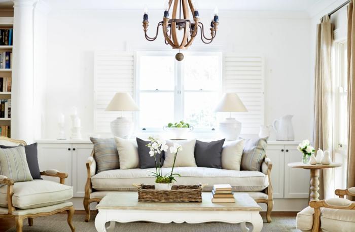 einrichtung und deko landhausstil, großes sofa mit vielen kissen, beige und dunkelgrau kombinieren, tisch aus marmor, sessel mit weichem sitzplatz, lüster