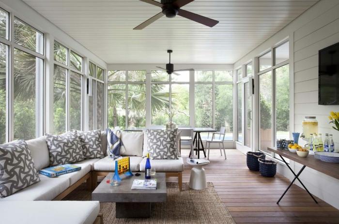wohnzimmer ideen modern, fenster aus allen seiten des zimmers, ecksofa mit marmortisch, großer fernseher und regal darunter