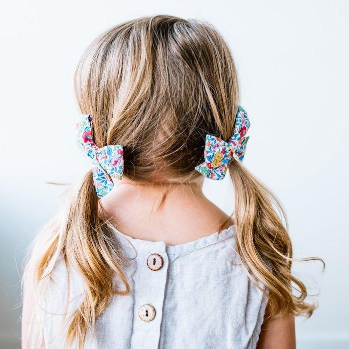 Schöne und leichte Frisuren für Mädchen, locker gebundene Haare, zwei Schleifen mit Blumenmuster, weißes Kleid
