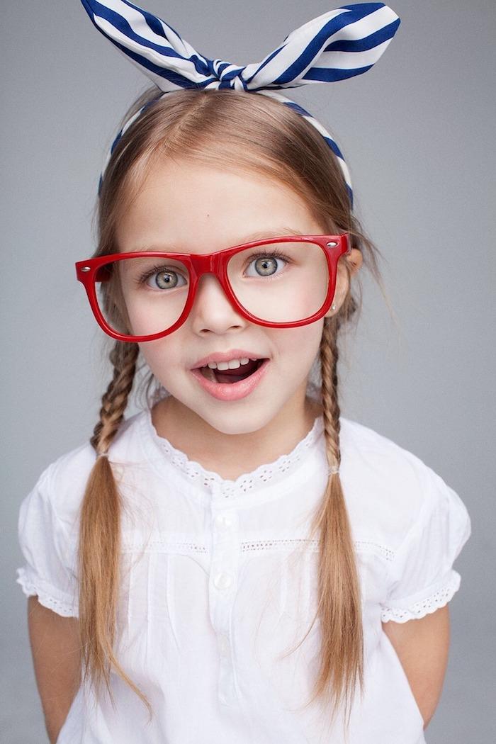 Tolle Kinderfrisuren zum Nachstylen, zwei Zöpfe und gestreiftes Haarband, weißes Hemd mit kurzen Ärmeln, Brille mit rotem Rahmen
