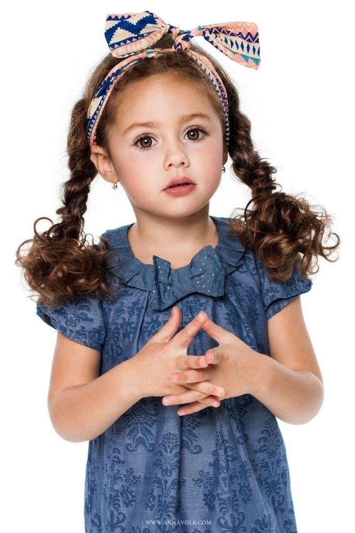 Schöne Frisuren für Mädchen, zwei Zöpfe und buntes Haarband, dunkelblaues Kleid mit kurzen Ärmeln