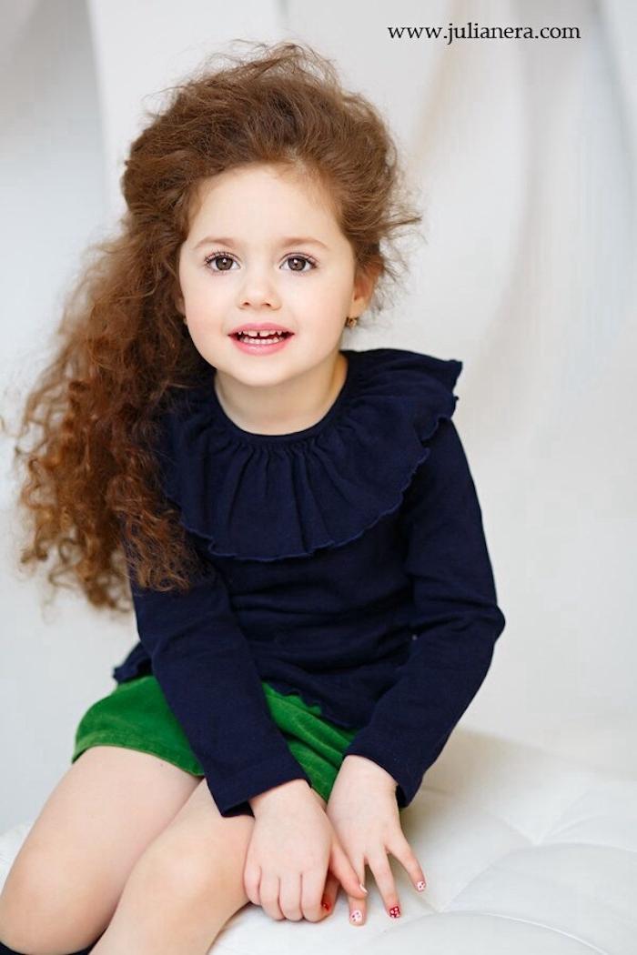 Lange lockige Haare, halboffene Frisur, dunkelblaue Bluse mit Kragen und grüner Rock