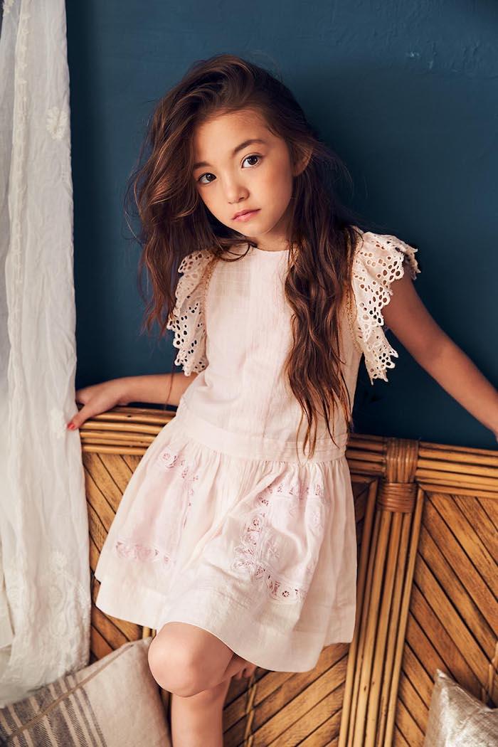 Lange offene Haare, weißes Kleid mit Spitzenelementen an den Ärmeln, braune Haare und braune Augen