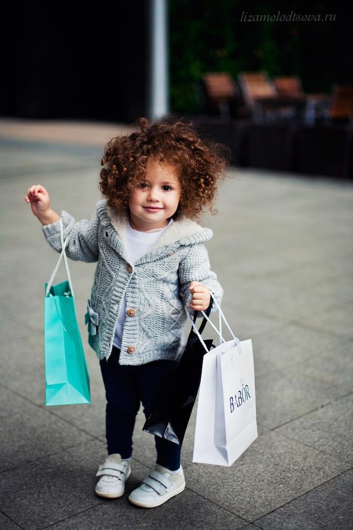 Süßes Mädchen mit mittellangen lockigen Haaren, grauer Cardigan und schwarze Hose, weiße Bluse und Sneakers