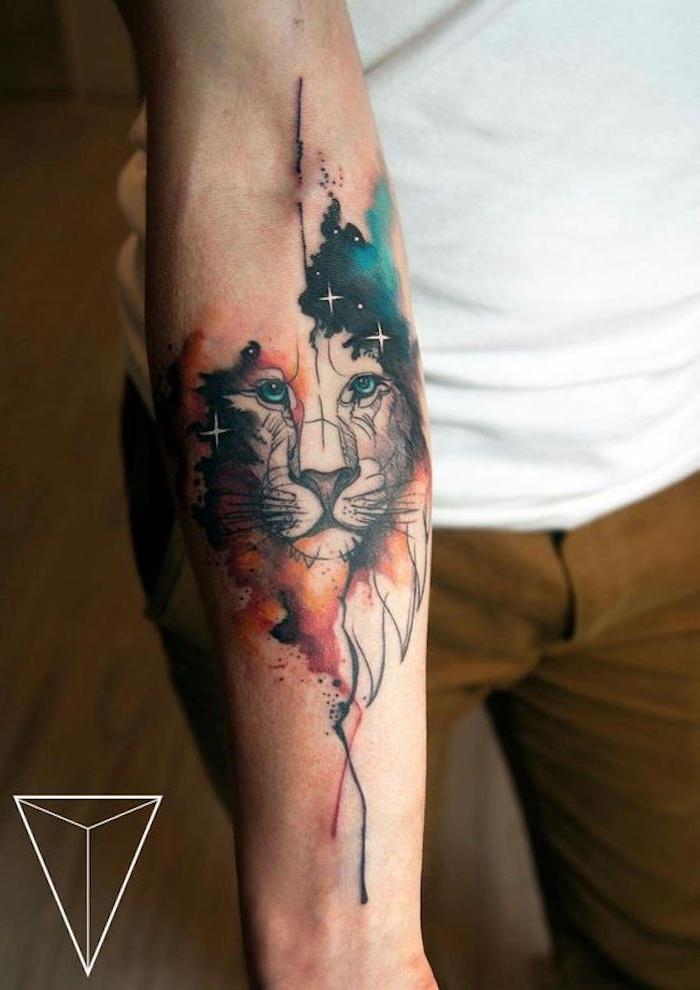 eine hand mit einem großen watercolor tattoo mit löwe mit blauen augen und einer roten mähne und mit einem himmel mit vielen kleinen weißen sternen