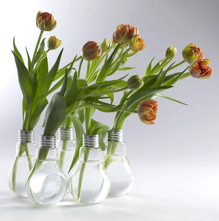 viele kleine vasen aus alten glühbirnen und mit wasser und orangen blumen mit grünen blättern, recycling basteln ideen