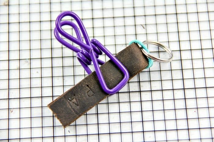 ein Streifen von Leder mit Wäscheklammern fixiert zum Trocknen, Schlüsselanhänger selber basteln