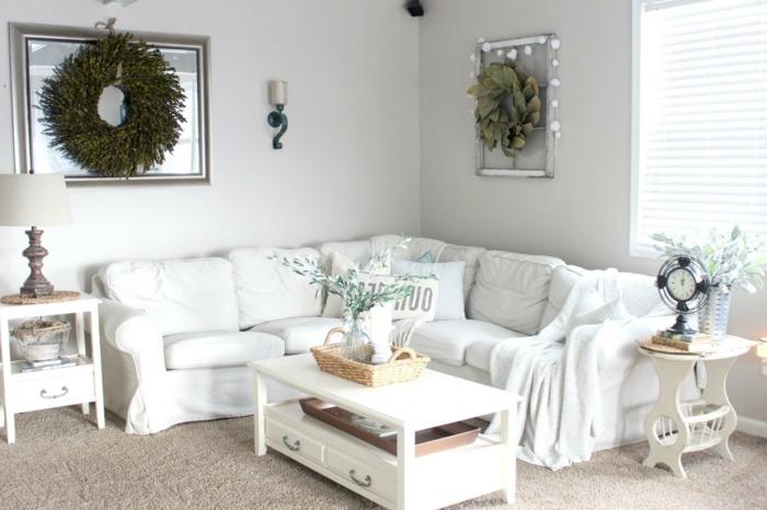 weiße landhausmöbel wohnzimmer, großer blumenkranz in grün hängt an der wand als deko, weißer tisch großes ecksofa
