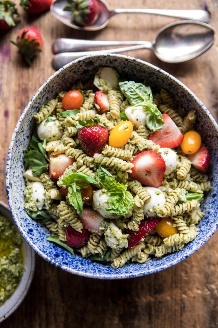 Erdbeeren, gelbe Traube, kleine gekochte Eier, grüne Nudeln, Salatblätter, Salat mit Avocado