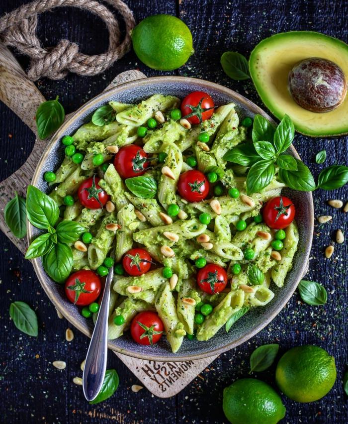 grüne Nudeln, rote Kirschtomaten, Erbsen, Limettensaft als Dekoration