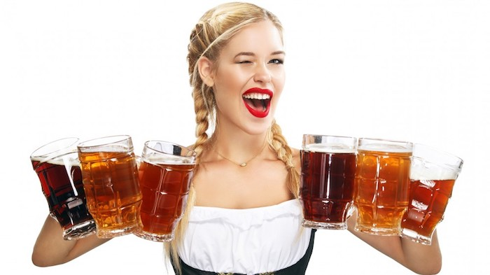 Blonde Frau in traditioneller bayerischer Trachtenkleidung, Bier servieren