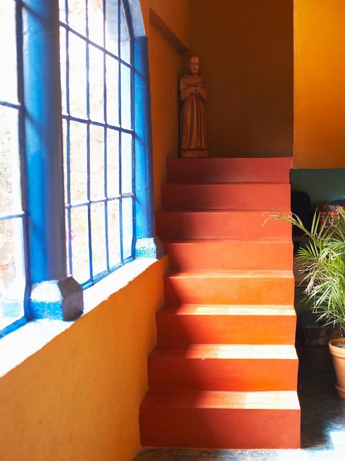 eine orange treppe und ein blaues fenster und eine orange wand und ein blumentopf mitmeiner orangen pflanze