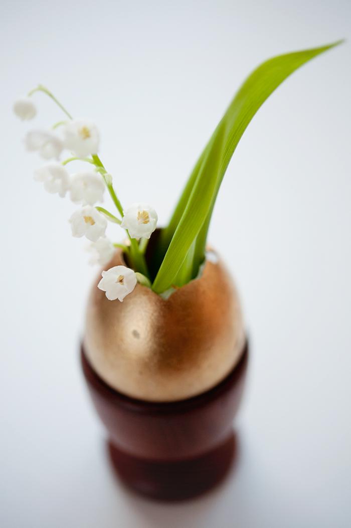 osterdeko selber machen, diy vase aus goldenem ei, kleine weiße blume, tischdeko