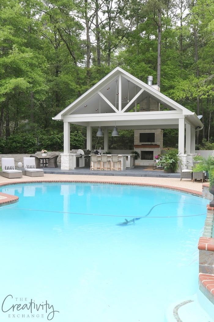 ein pool mit wasser und ein weißes haus mit einer küche mit einem waschbecken und zwei grauen lampen