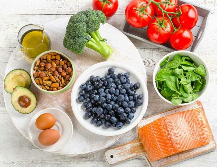 10 regeln der dge, gesundes essen selber kochen, lachs mit salat aus spinat, tomaten, avocado, eier und mandeln, brokkoli als beilage und blaubeeren zum nachtisch