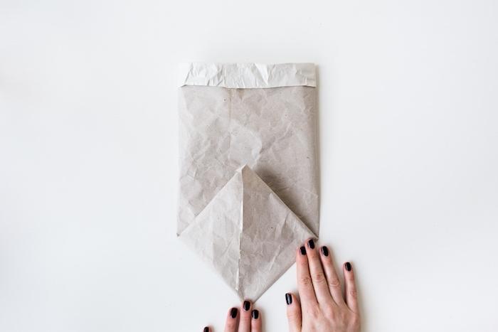 upcycling basteln ideen, eine hand mit einem schwarzen nagellack und eine gefaltete kleine weiße papiertüte basteln