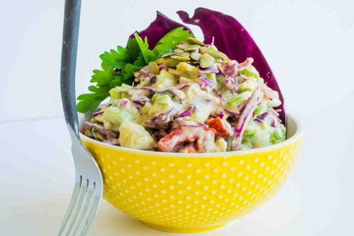 eine gelbe Schale, verschiedene Gemüse, Paprika, roter Zwiebel, Kürbiskerne, Petersilie, raffinierte Salate