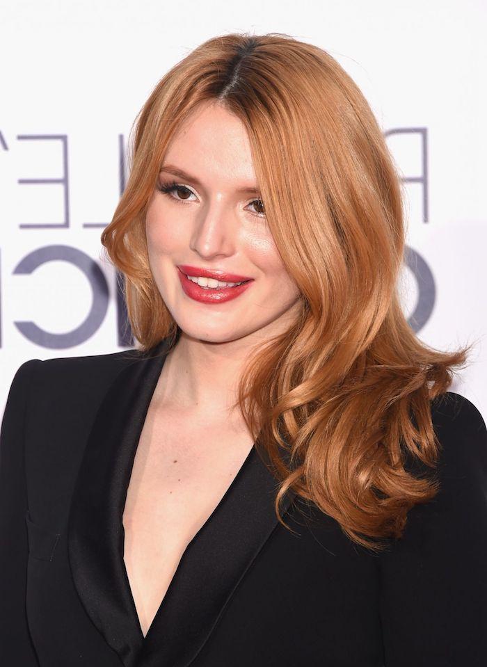 Kupferfarbene Haare mit dunklem Haaransatz, roter Lippenstift und schwarze Mascara, schwarzer Blazer
