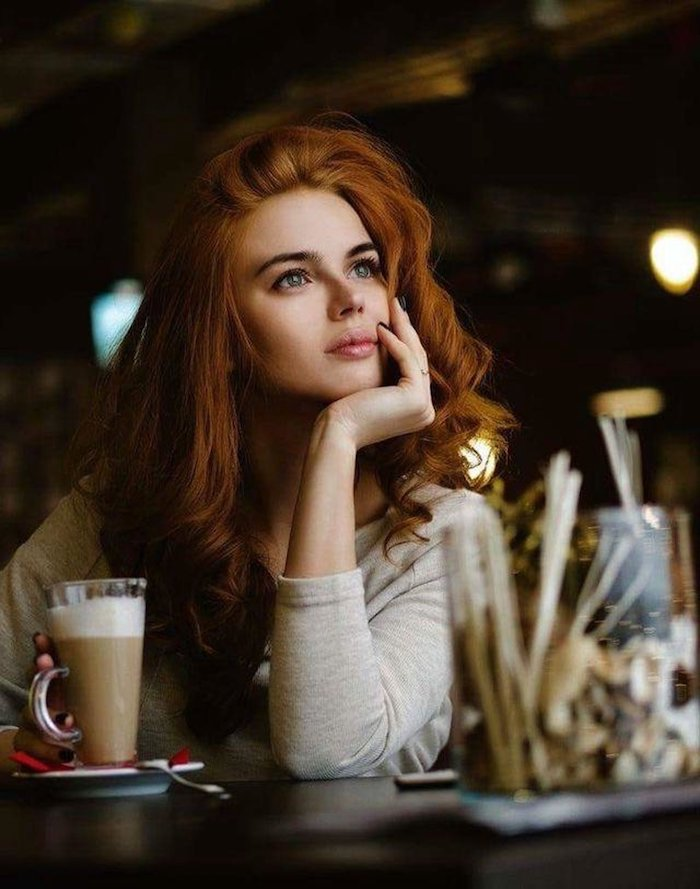 Lange wellige kupferfarbene Haare, leichtes Tages Make-up, Bluse mit langen Ärmeln in Beige