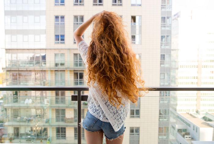 Lockige kupferfarbene lange Haare, weißes Top mit Spitzenelenemten und Denim Shorts
