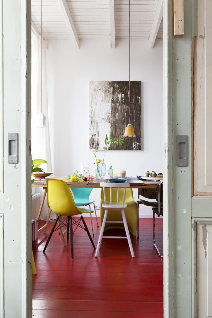 schwatzes und weißes Bild, Esszimmer mit bunten Stühlen und rotem Boden, schöne Farbkombinationen