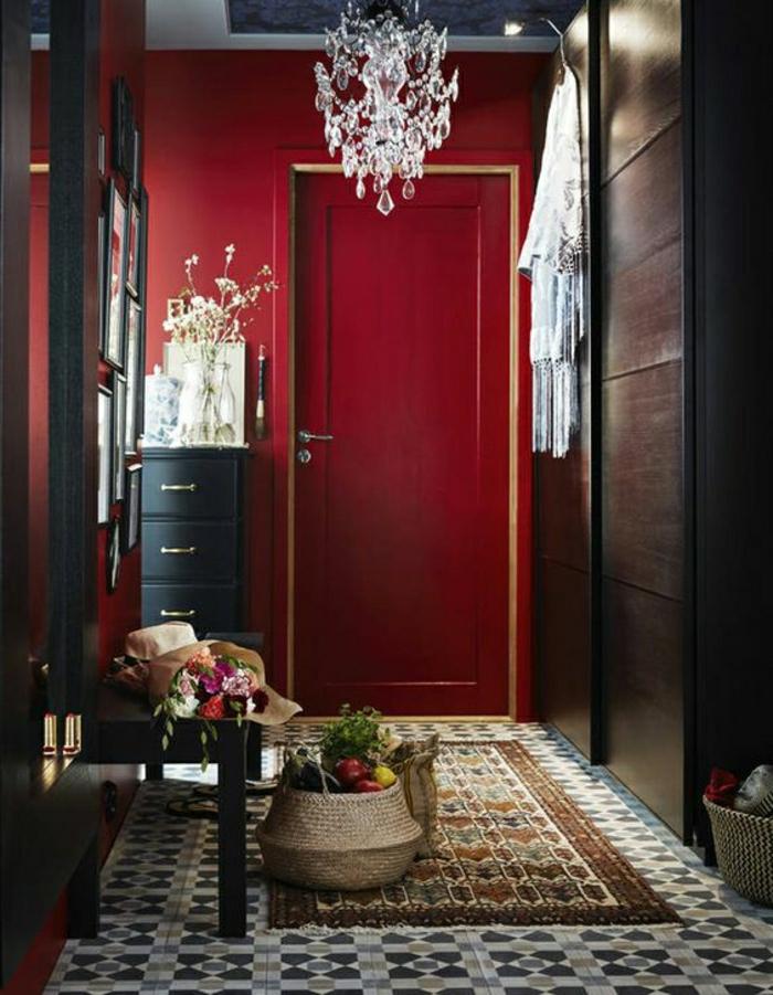 ein Flur mit roten Wände, schwarzer Schuhschrank, gläserne Kronleuchte, schöne Farbkombination