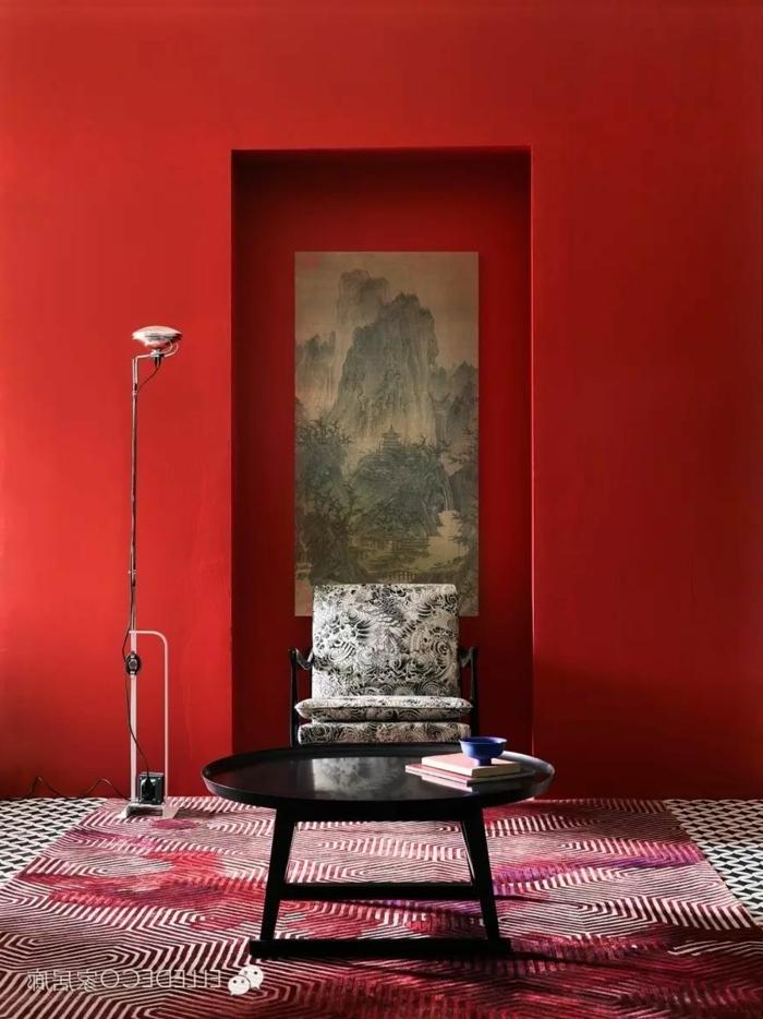 rote Wände, graues Bild, ein schwarzer Tisch, gestreifter Teppich, schöne Farbkombinationen