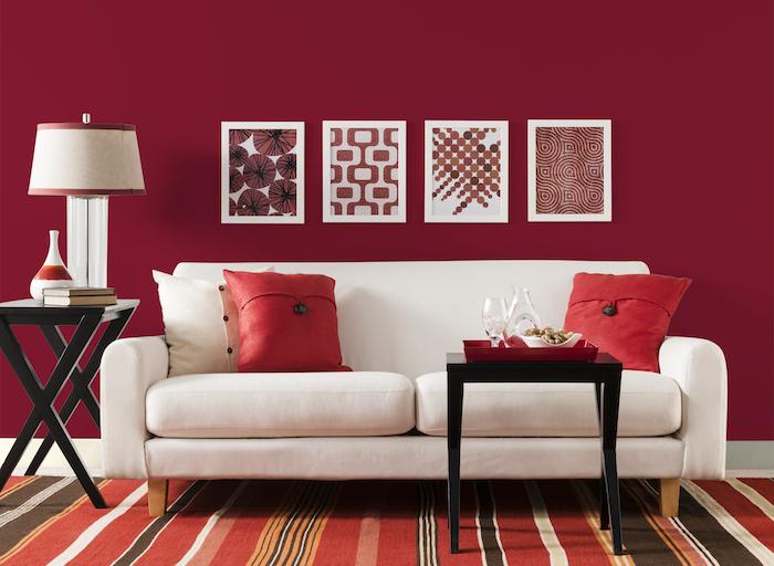 eine große rote wand mit roten bildern mit weißen bilderrahmen, ein weißes sofa mit roten und weißen kissen und ein kleiner schwarzer tisch und eine weiße lampe und ein roter teppich