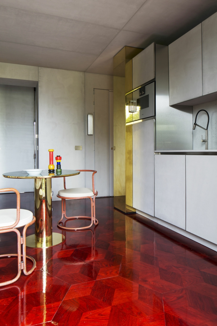 ein roter Boden, Küchenfarbe, ein kleiner runder Tisch, weiße Regale, Farben, die zusammenpassen