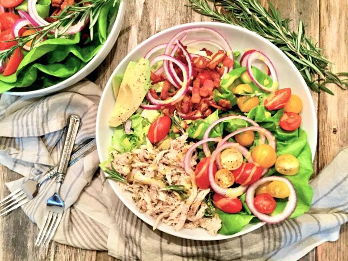 Avocado Tomaten Salat mit Kirschtomaten in zwei Farben, Zwiebelringe, einige Stücke Fleisch