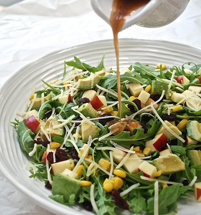 Rucola, eine braune Soße, Mais, Avocado, Apfel, raffinierte Salate zum Genießen