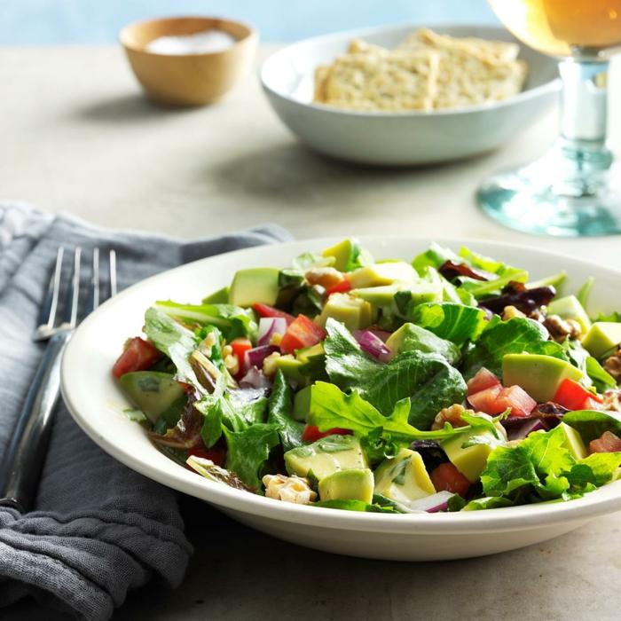 raffinierte Salate, Avocado, grüne Salatblätter, roter Paprika und weißes Dressing
