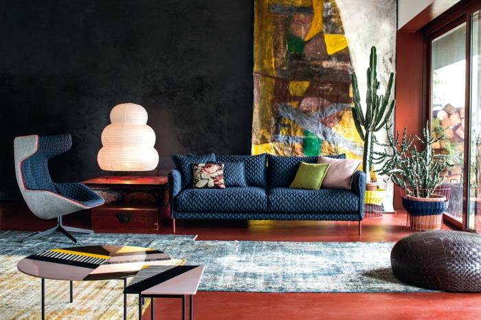 ein blaues Sofa, eine weiße Lampe, ein blauer und ein gelber Teppich, Farben, die zusammenpassen