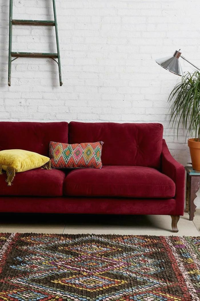 Bordeauxrotes Sofa, weiße Wand, bunter Teppich, welche Farbe passt zu Bordeauxrot