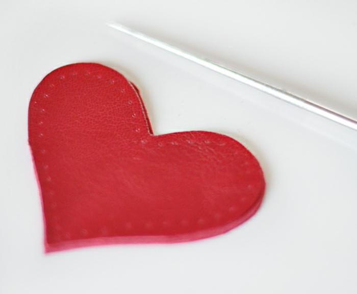 ein rotes Herz mit Ahle perforiert, damit Sie die Fäden einfädeln können, Schlüsselanhänger selber machen