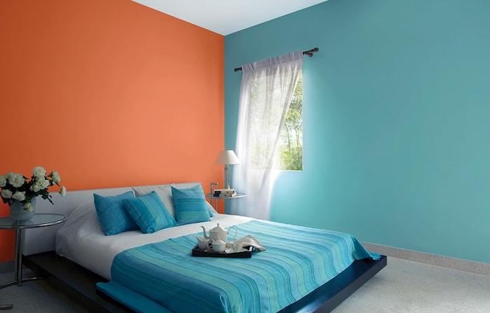 bett mit blauen kleinen kissen und einer blauen decke, eine blaue wand und eine orange wand und ein fenster mit einem weißen vorhang, wand farbig streichen