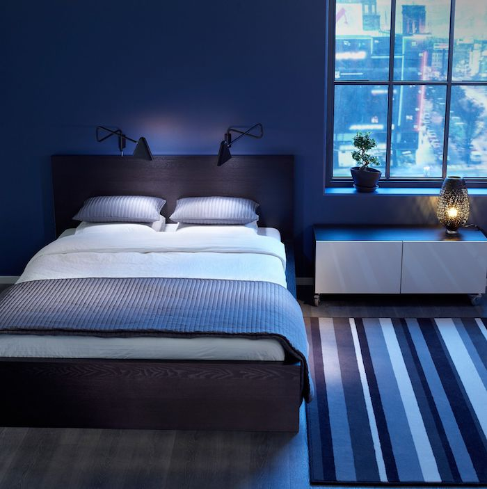 ein boden aus holz und mit einem blauen teppich, schlafzimmer streichen ideen, ein schlafzimmer mit einem bett mit blauen 8und weißen kissen und ein blauer teppich