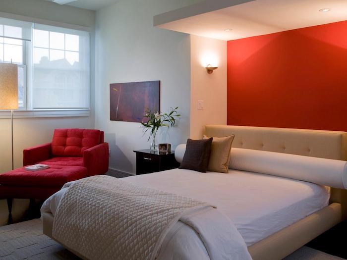 eine rote wand in einem schlafzimmer mit einemn bett mit kleinen violetten und beigen kissen und mit einem roten sofa und einer gelben lampe, schlafzimmer streichen ideen