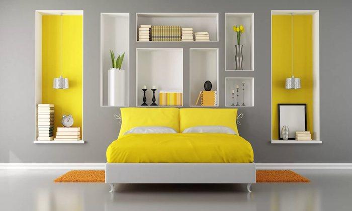 eine große graue wand in einem schlafzimmer mit einem gelben bett mit gelben und weißen kissen, weiße vase mit grünen pflanzen und gelben blumen, wandfarbe gelb