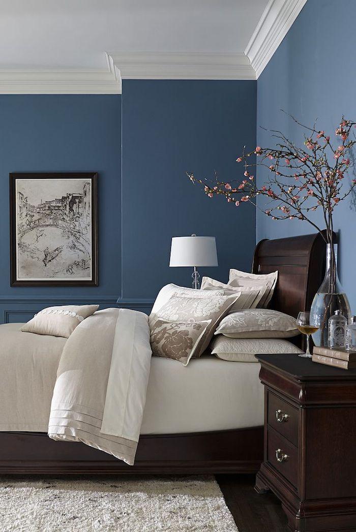 große blaue wände und ein bett mit weißen kissen und einer weißen decke , eine große blaue wand und ein bild und eine vase mit ästen mit pinken blättern, schlafzimmer einrichten, wandfarbe schlafzimmer