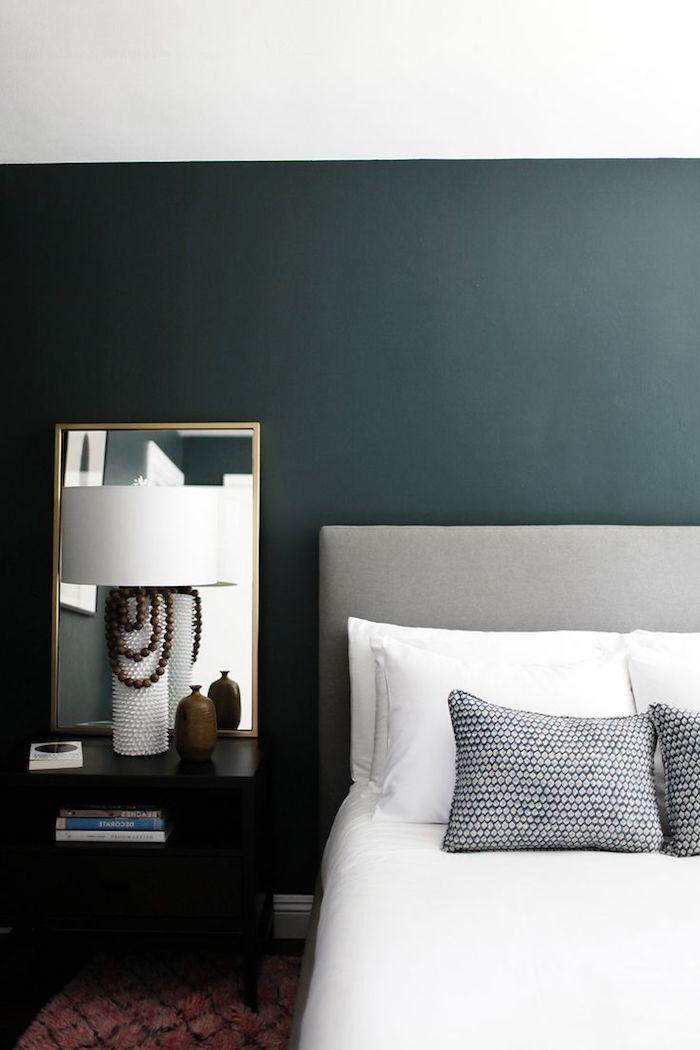 ein spiegel und eine kleine weiße lampe und ein bett mit weißen und grauen kissen und eine grüne wand, wände streichen farbideen