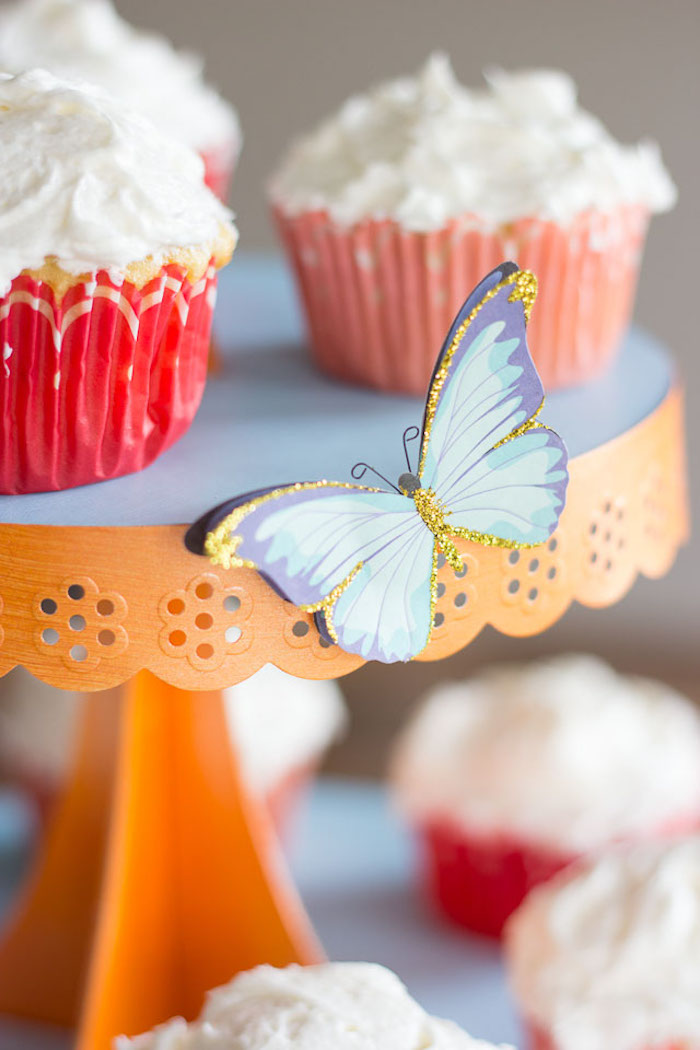 Blauer Schmetterling aus Papier, dekoriert mit goldenem Glitter, Cupcakes mit Sahne