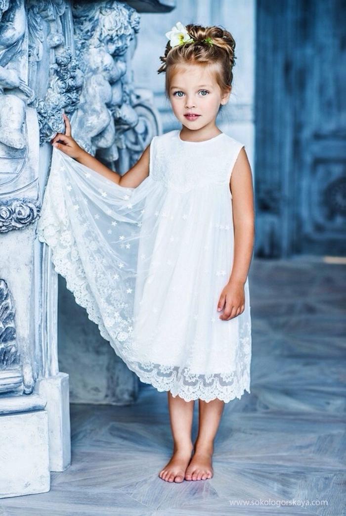 Elegante Hochsteckfrisur für Mädchen, echte Blumen im Haar, weißes langes Kleid ohne Ärmel
