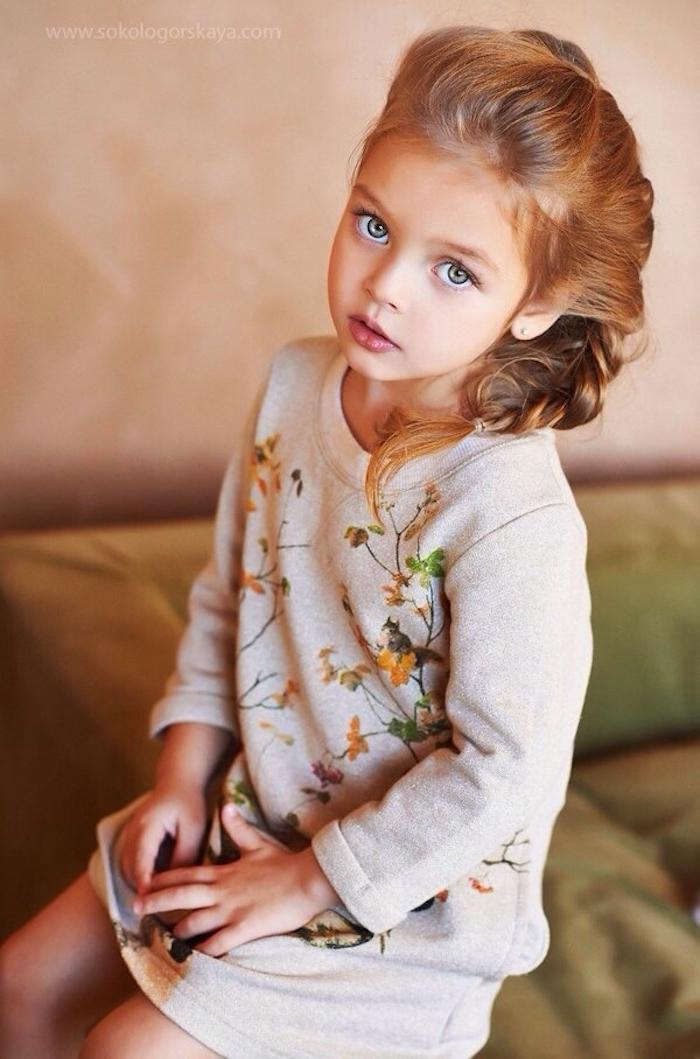 Schöne seitliche Flechtfrisur, dunkelblonde Haare und blaue Augen, weißes Kleid mit langen Ärmeln