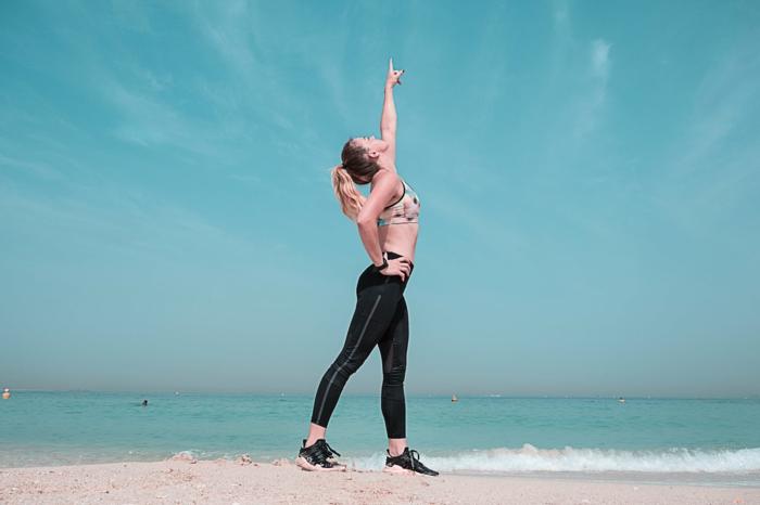 schulterlange haare stylen, ideen für frisuren während training, gebundene haare, ojmbre blond, foto am strand, frau geht laufen an der meerküste