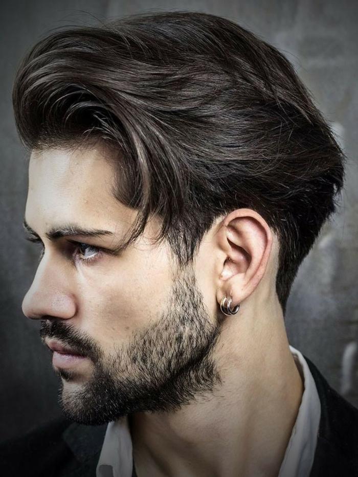 lange Haare, schwarzer Bart, kleine runde Ohrringe, braune Augen, ein Hemd und Jacke
